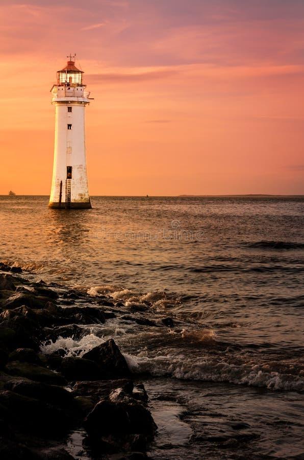 Phare de roche de perche au coucher du soleil photo stock