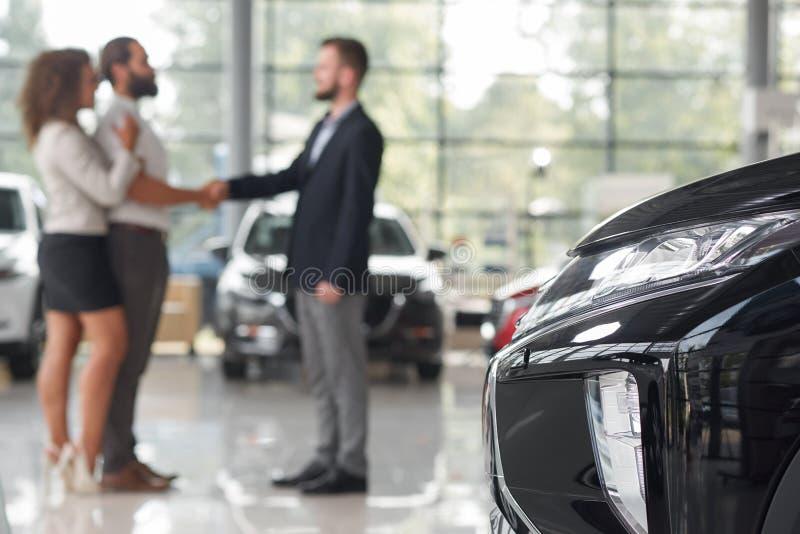 Phare de voiture, couple faisant l'affaire avec le concessionnaire automobile derrière photos stock