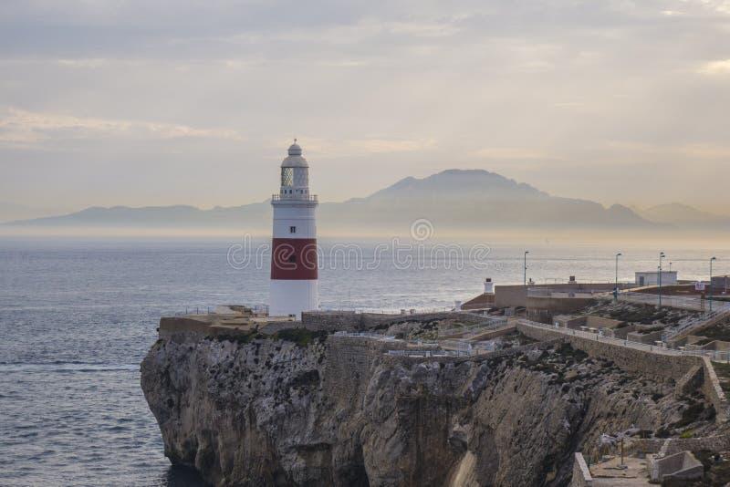 Phare du Gibraltar sur la falaise par la mer avec des montagnes dedans loin image libre de droits