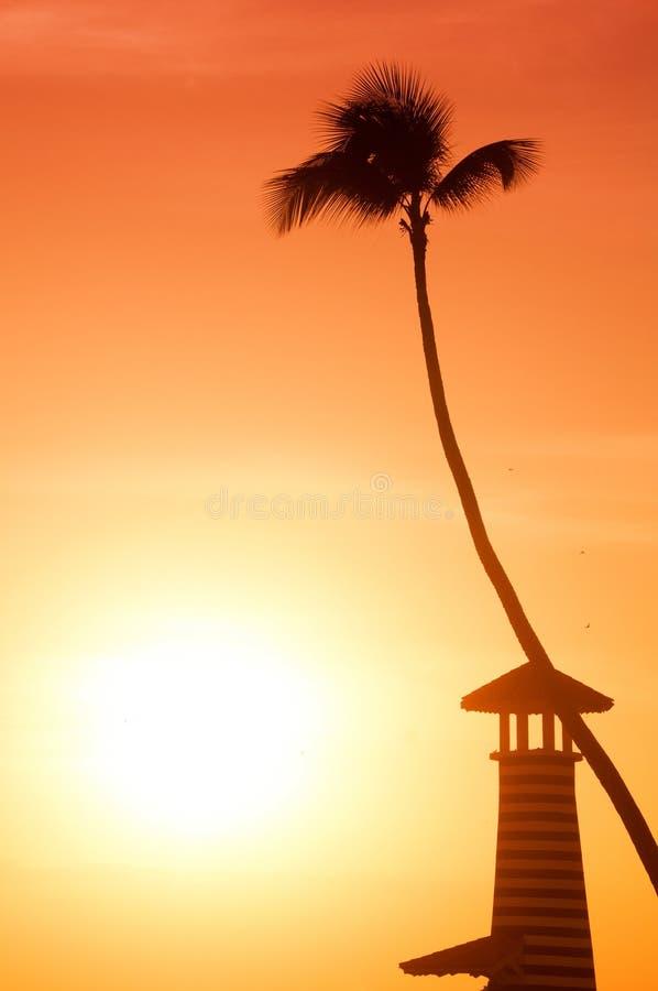 Phare et palmier sur le fond d'un coucher du soleil orange photographie stock libre de droits