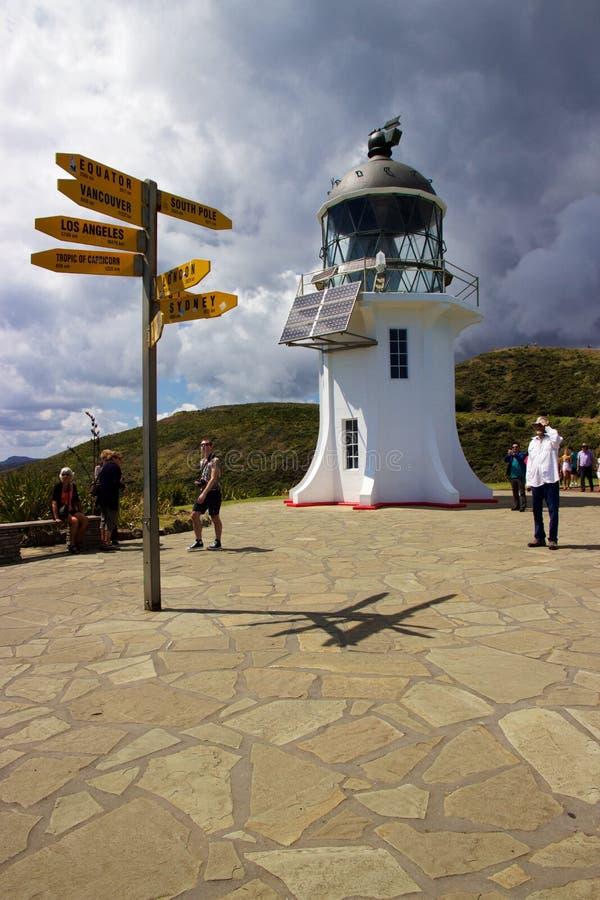 Phare et poteau indicateur au cap Reinga, la terre du nord, Nouvelle-Zélande image stock