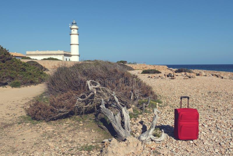 Phare et valise rouge sur un rivage rocheux chez Cap de Ses Salines photo stock