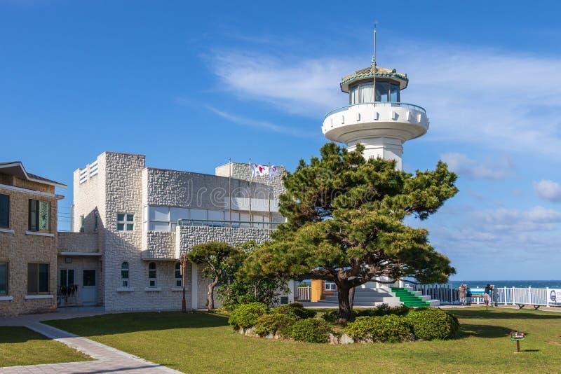 Phare principal de Ganjeolgot, lumière supérieure de direction, avec des bâtiments et des drapeaux coréens près de point situé le photographie stock libre de droits