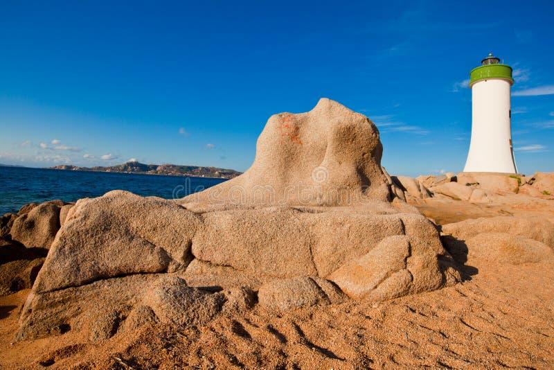 Phare, roches rouges et sable. image libre de droits