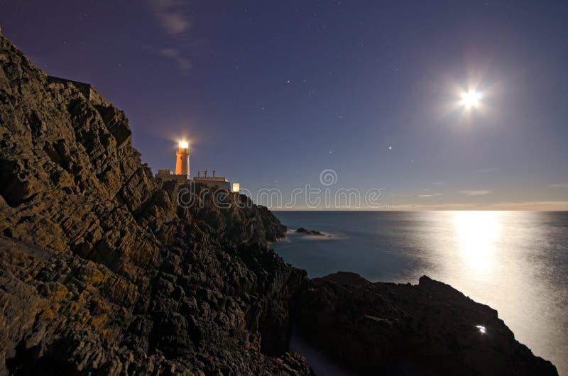 Phare sur des falaises avec le ciel de nuit photos stock