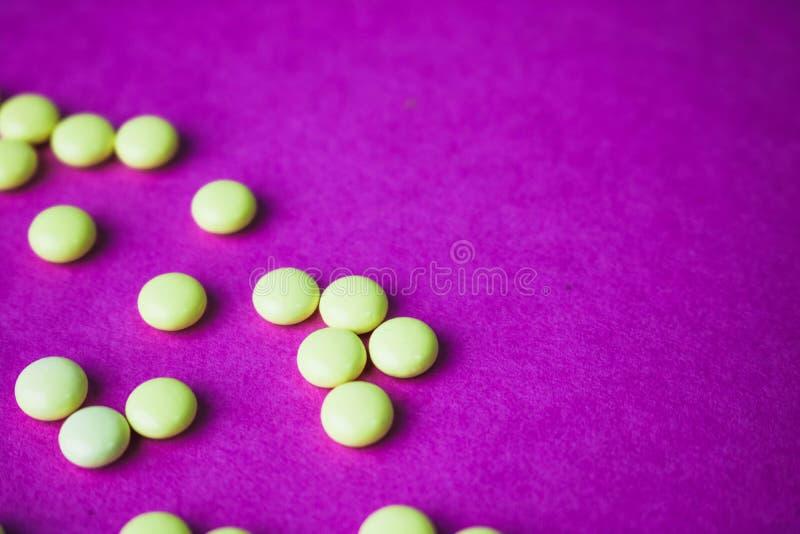 Pharmaceptic runda piller för liten gul orange härlig läkarundersökning, vitaminer, droger, antibiotikummar på en rosa purpurfärg royaltyfria bilder