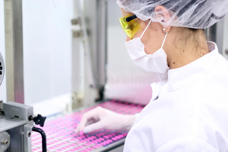 Pharmaceutical Factory - Quality Control. Technician inspecting the quality of pills at a pharmaceutical factory royalty free stock photo