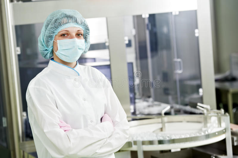 Pharmaceutical factory worker. Pharmaceutical factory woman worker in front of production line at pharmacy industry manufacture factory royalty free stock photo