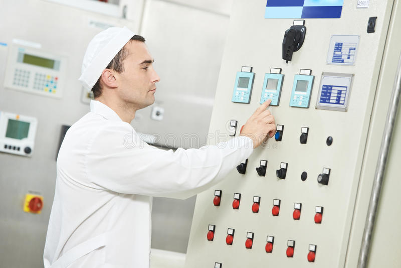 Pharmaceutical factory worker. Pharmaceutical factory man worker operating water preparation production line at pharmacy industry manufacture factory stock image