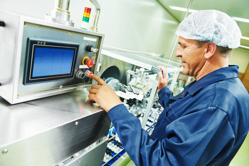 Pharmaceutical factory worker. Pharmaceutical factory man worker operating production line at pharmacy industry manufacture factory stock images