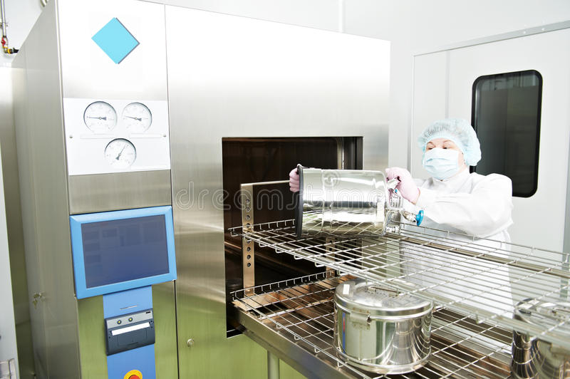 Pharmaceutical factory worker. Pharmaceutical factory woman worker operating autoclave for medicine drug steam sterilization at pharmacy industry manufacture stock photos