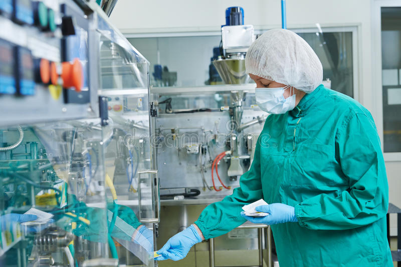 Pharmaceutical factory worker. Pharmaceutical factory woman worker operating production line at pharmacy industry manufacture factory royalty free stock image