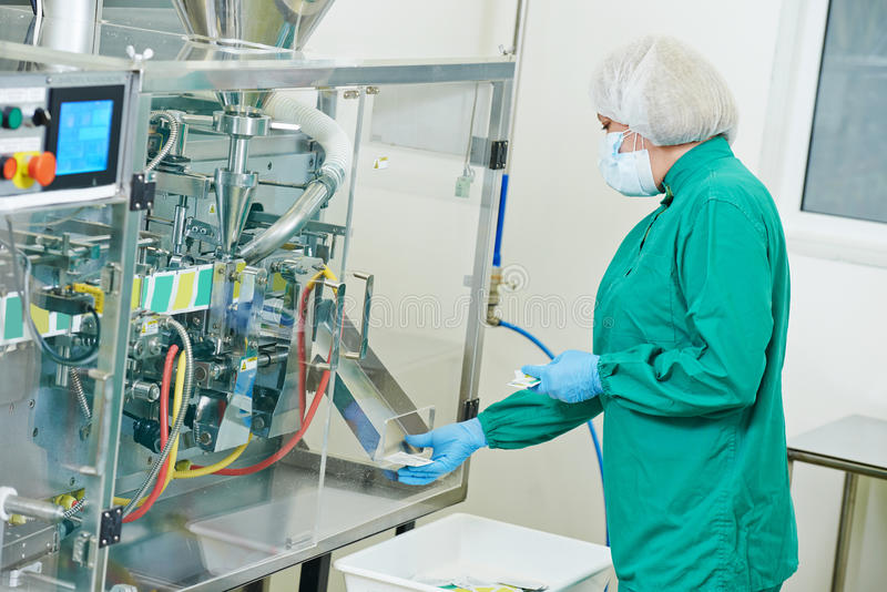 Pharmaceutical factory worker. Pharmaceutical factory woman worker operating production line at pharmacy industry manufacture factory stock photography