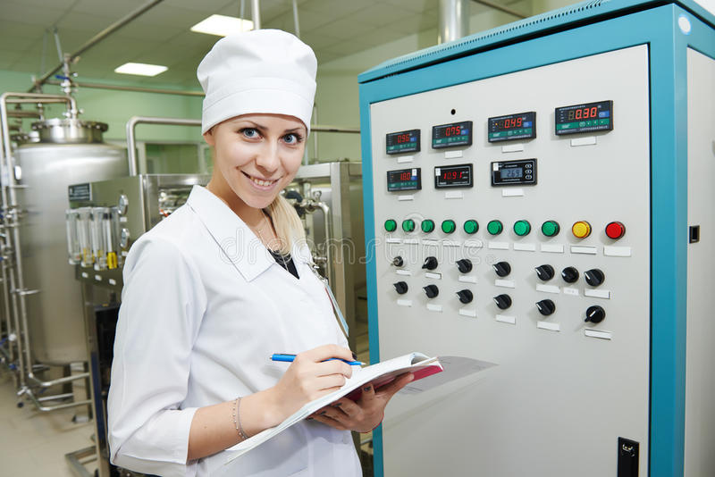 Pharmaceutical factory worker. Pharmaceutical factory woman worker operating water preparation production line at pharmacy industry manufacture factory stock photo