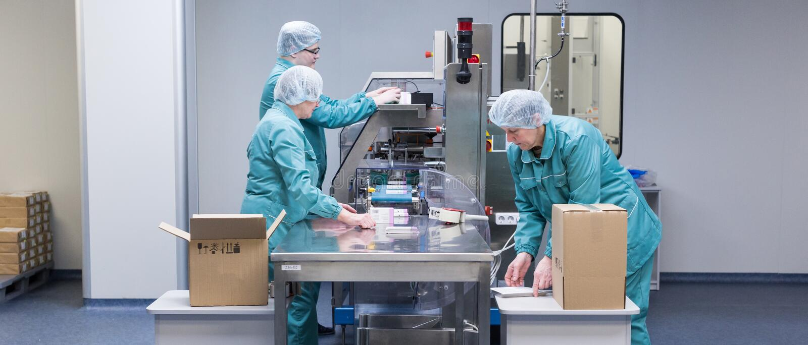 Pharmaceutical factory workers in sterile environment stock images