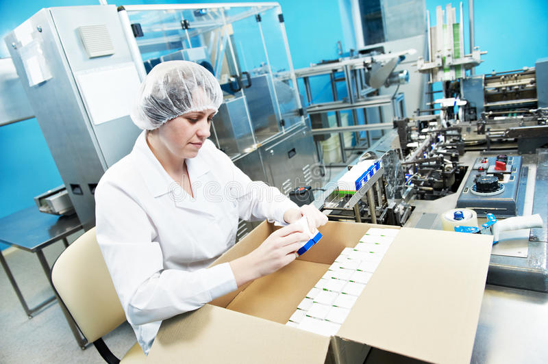 Pharmaceutical industrial factory worker. Pharmaceutical factory worker at pharmacy industry manufacture packing medicine into boxes royalty free stock photos