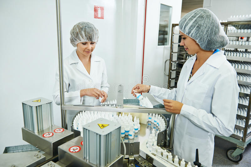 Pharmaceutical industrial factory worker. Two pharmaceutical factory workers at pharmacy industry manufacture checking medicine on conveyer royalty free stock photo