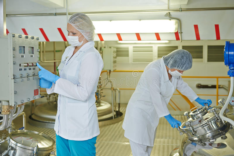 Pharmaceutical industry factory worker. Pharmaceutical factory workers with equipment mixing tank on production line in pharmacy industry manufacture factory royalty free stock images