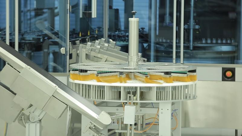 Pharmaceutics. Line machine conveyer for packaging glass bottles ampoules in boxes at factory. pharmaceutical medicine. Pharmaceutical industry. Production stock photo