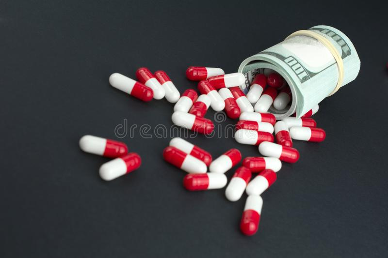 Red white pills spill out of folded dollars royalty free stock photography