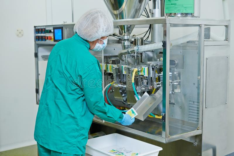 Pharmaceutical industry. technician works with medicine packing machine. Pharmaceutical industry. Factory technician works with medicine packing machine stock images