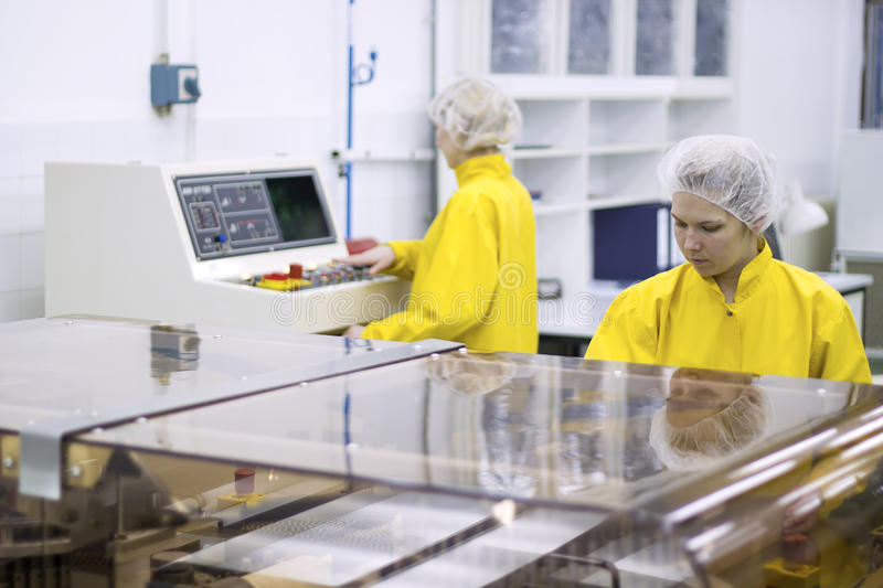 Pharmaceutical Manufacturing Technicians on the Production Line. Two pharmaceutical workers wearing protective work wear. Female workers at pharmaceutical royalty free stock photo