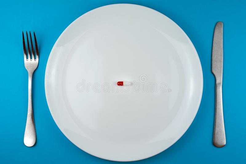 Pharmaceutical pill or capsule on a plate with a fork and knife royalty free stock image