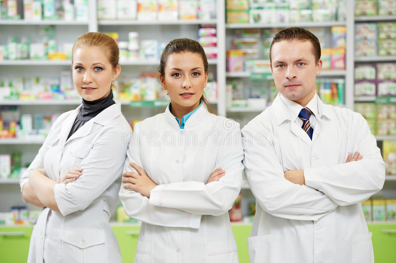 Pharmaceutist woman and man workers in drug store stock photography