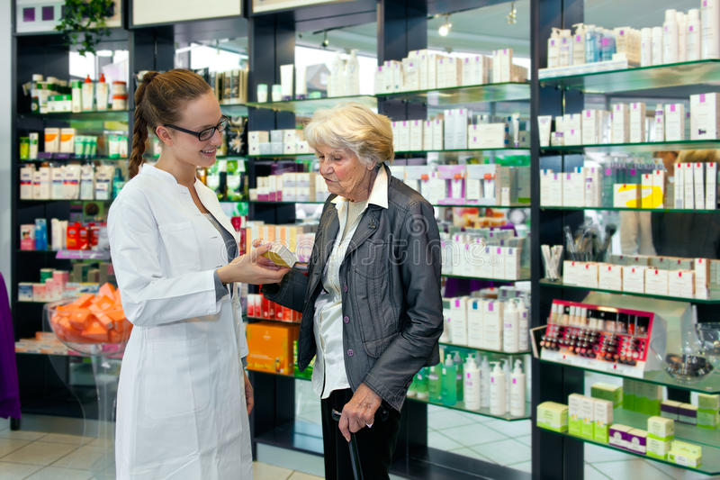 Pharmacien aidant une dame supérieure image libre de droits