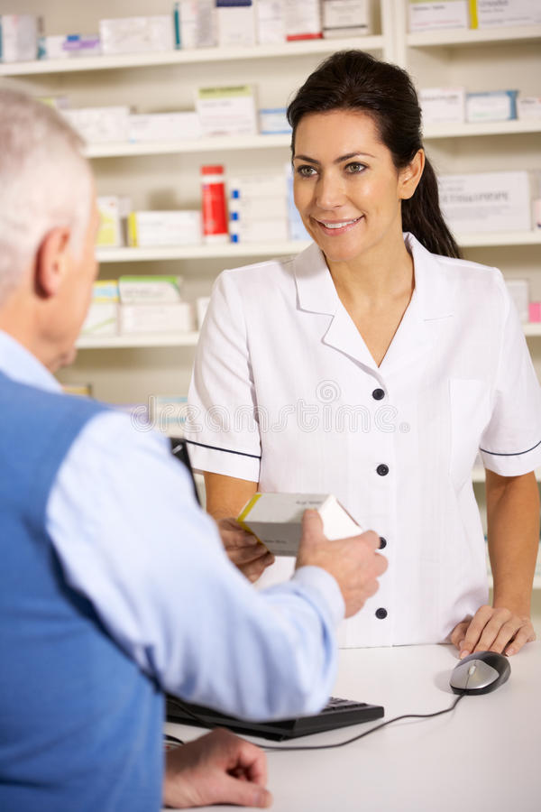 Pharmacien américain distribuant à l'homme aîné photo stock