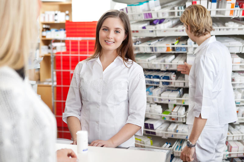 Pharmacien Attending Customer au compteur images stock