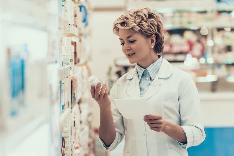 Pharmacien avec la bouteille de pilules dans le magasin de pharmacie images libres de droits