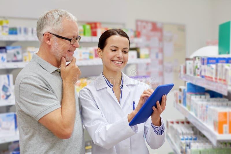 Pharmacien avec le PC de comprimé et l'homme supérieur photographie stock libre de droits