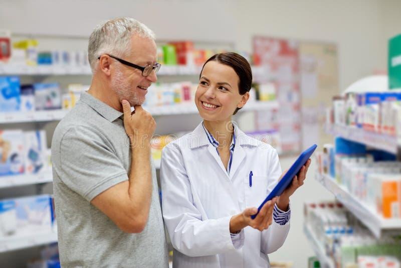 Pharmacien avec le PC de comprimé et l'homme supérieur photo stock