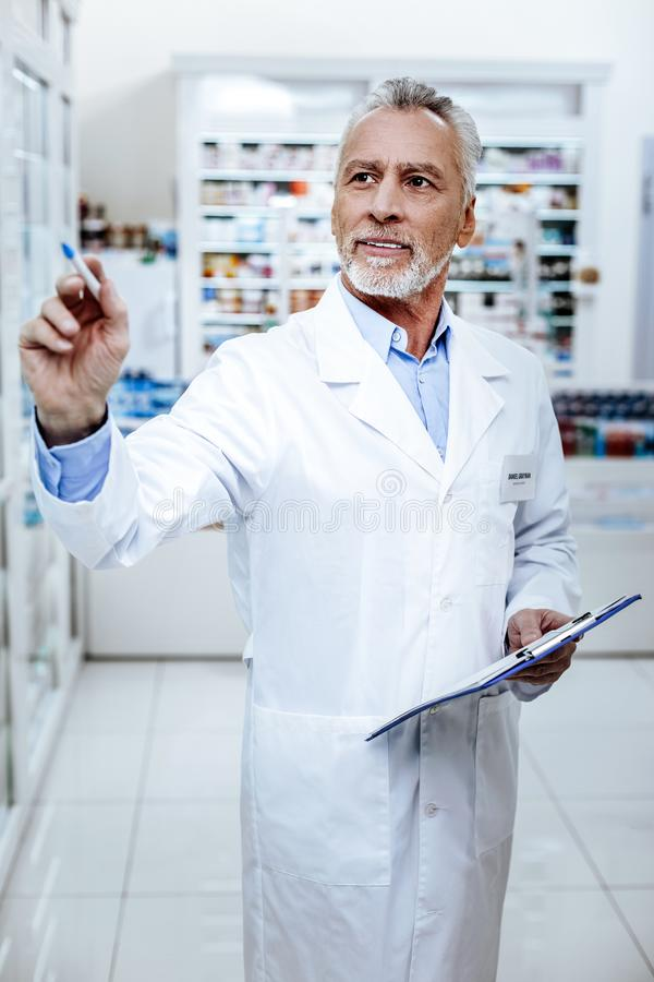 Pharmacien barbu beau dans un manteau blanc semblant occupé photo stock