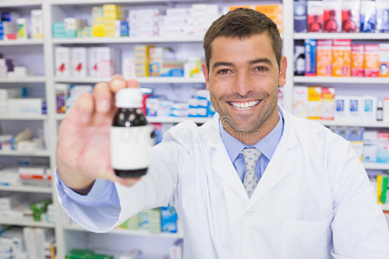 Pharmacien beau montrant la bouteille de médecine image stock