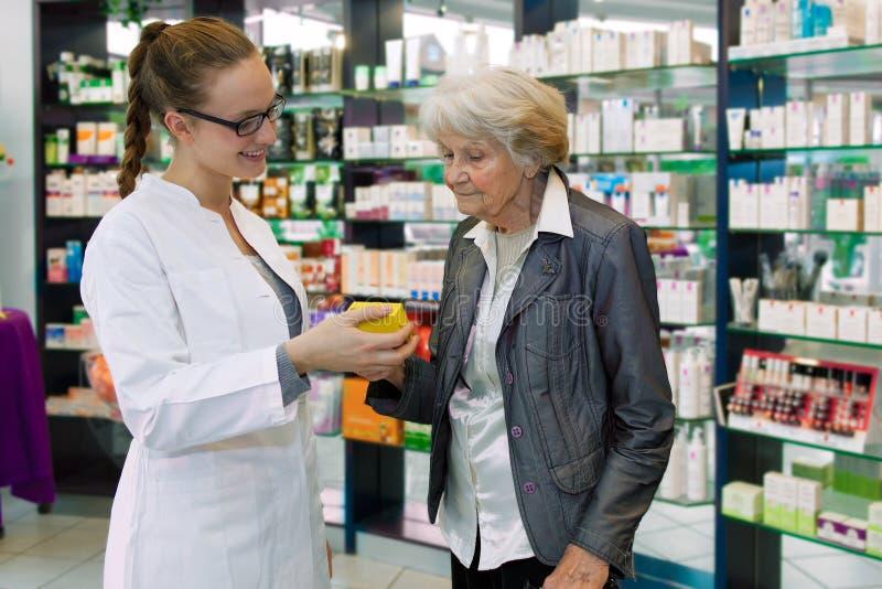 Pharmacien conseillant le médicament au patient supérieur. photo stock