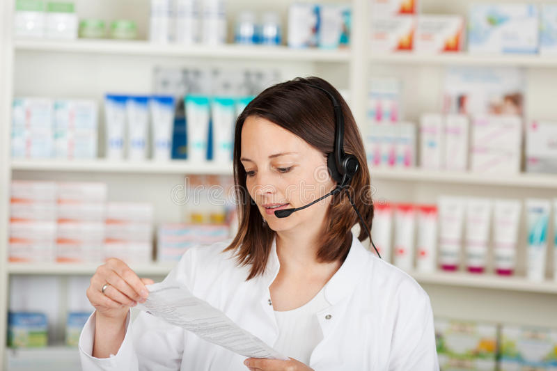 Pharmacien Conversing On Headset dans la pharmacie image stock