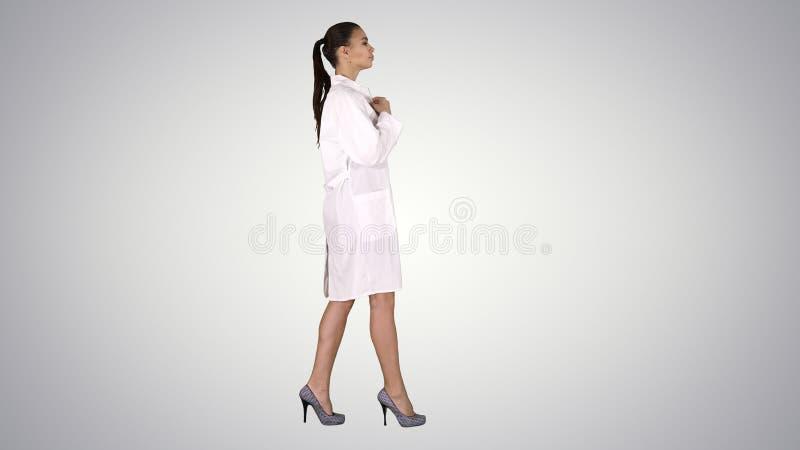 Pharmacien de jeune femme dans l'uniforme blanc de manteau de robe marchant sur le fond de gradient photographie stock libre de droits