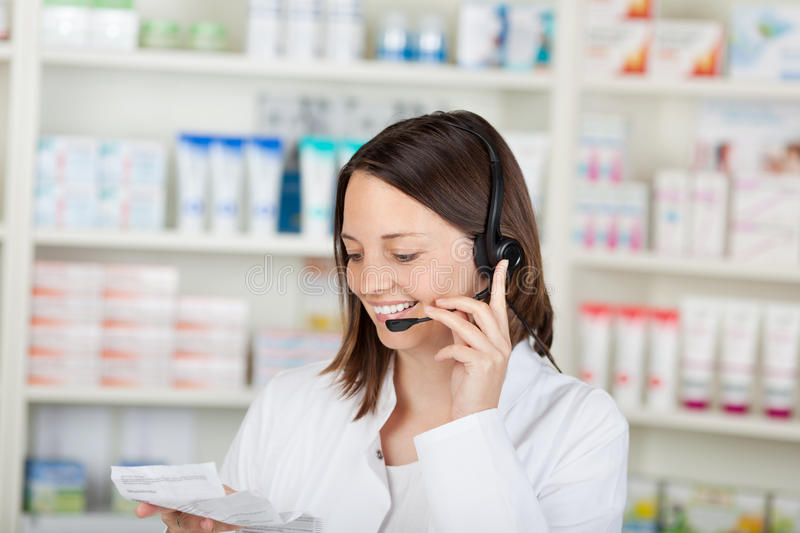 Pharmacien de sourire Conversing On Headset dans la pharmacie photographie stock