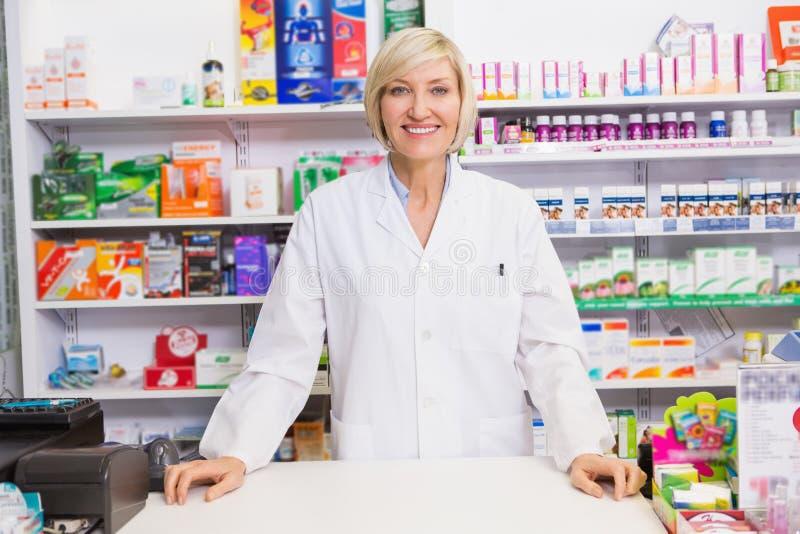 Pharmacien de sourire posant derrière le compteur photographie stock libre de droits