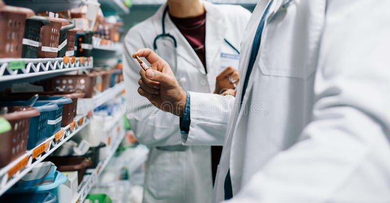 Pharmacien deux recherchant la drogue médicinale critique photographie stock
