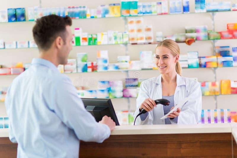Pharmacien et client à la pharmacie photographie stock libre de droits
