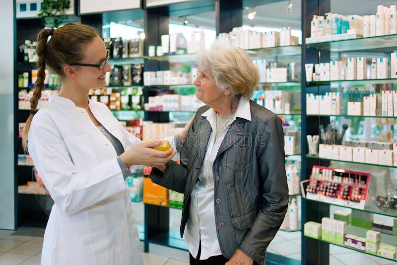 Pharmacien et femme supérieure reconnaissante photos stock