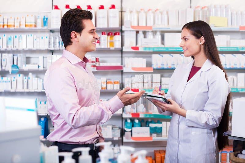 Pharmacien et homme de consultation dans la pharmacie image libre de droits