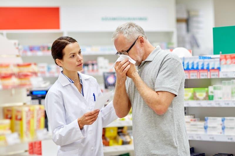 Pharmacien et homme supérieur avec la grippe à la pharmacie photographie stock libre de droits