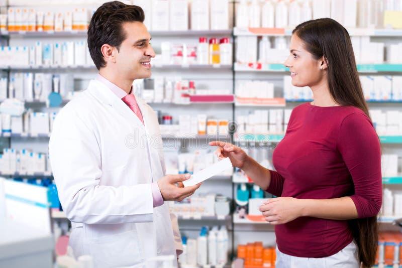 Pharmacien expérimenté conseillant le client féminin image stock