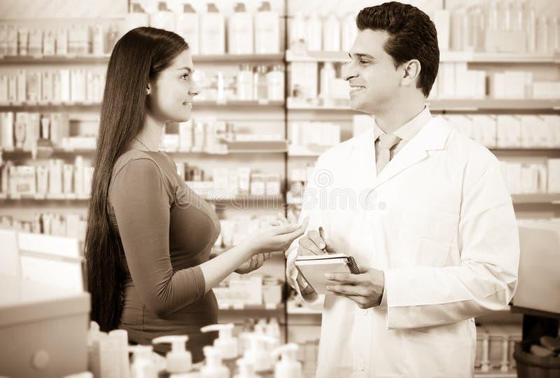Pharmacien expérimenté conseillant le client féminin photo libre de droits