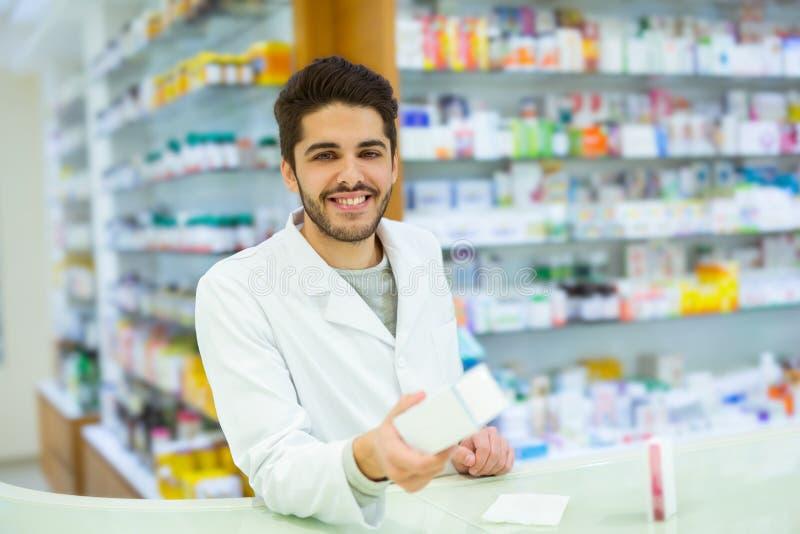 Pharmacien expérimenté conseillant le client féminin dans la pharmacie photo libre de droits