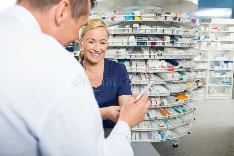Pharmacien Explaining Product Details au mâle photographie stock libre de droits
